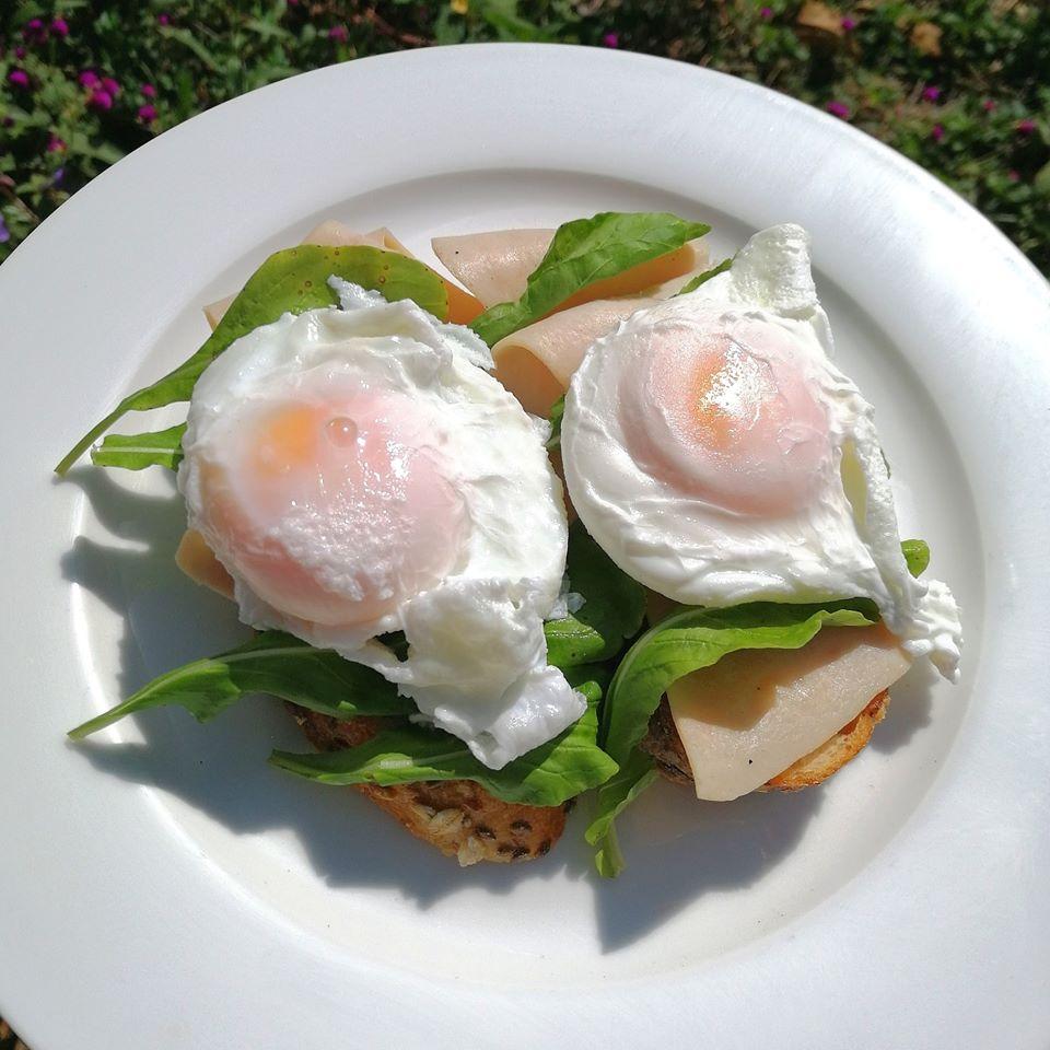 poached eggs over cereal bread at Pura Vida Encuentro